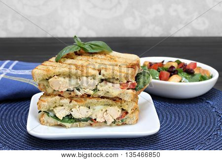 A chicken cheese pesto basil tomato and spinach panini stacked on a white plate. Macro image.