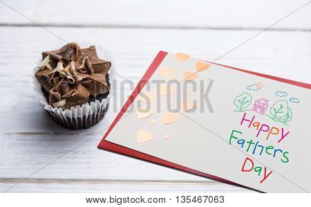Word happy fathers day on white background against chocolate cupcakes on a table