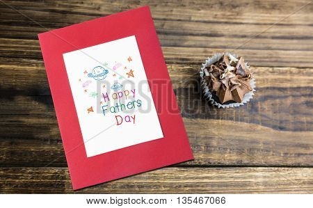 Word happy fathers day and space drawn against chocolate cupcakes on a table