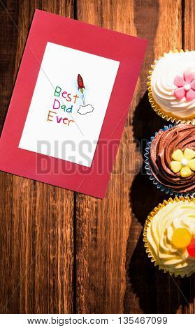 Word best dad ever on white background against delicious cupcakes on a table