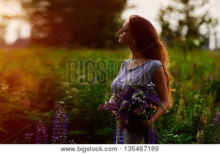 Woman holding a bouquet of blue lupine flowers in evening