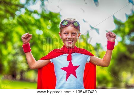 Little boy pretending to be superhero in park