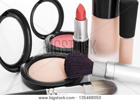 Elegant makeup collection. Foundation concealer face powder blush lipstick brushes.