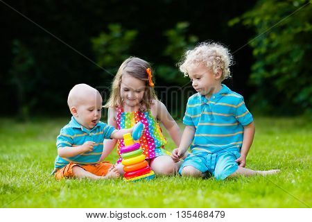 Three little children play with colorful rainbow pyramid toy. Educational toys for young child. Sibling kids building tower together. Toddler boy preschooler girl and baby build blocks outdoors.