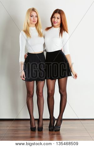 Clothing fashion people concept. Shot of full length ladies. Two beutiful young women wearing black skirt and white blouse. One girl is blonde second mulatto.