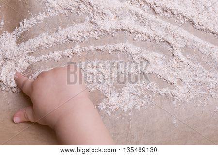 Child Hand Paints On Flour