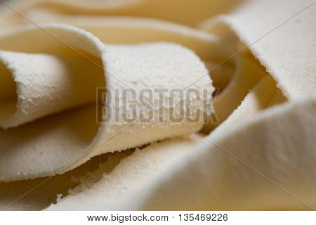 Homemade fettuccine pasta dry italian pasta rolled on blurred background