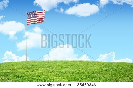 Flag of America on pole against blue sky over green field