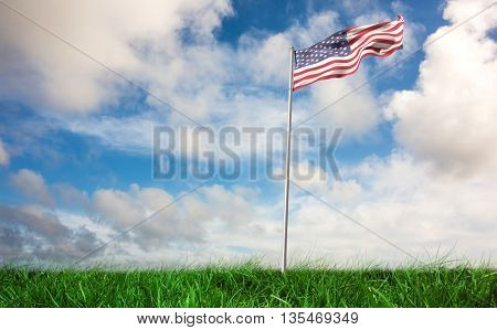 Low angle view of American flag against green grass under blue sky