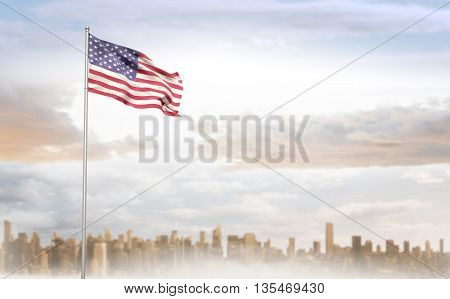 American flag waving on pole against large city on the horizon