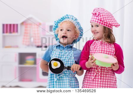 Little girl and boy in chef hat and apron cooking fried eggs in toy kitchen. Wooden toys for young children. Kids play and cook at home or daycare. Toddler kid playing with stove pans and dishes.