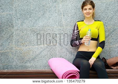 Fitness woman sitting and resting on bench after sport
