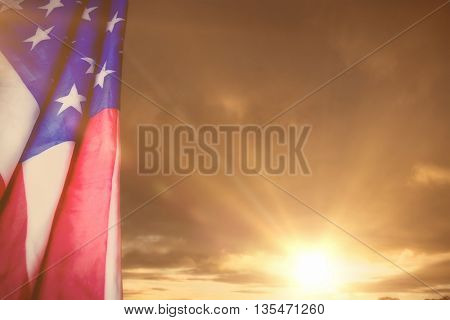 Creased US flag against cloudy sky