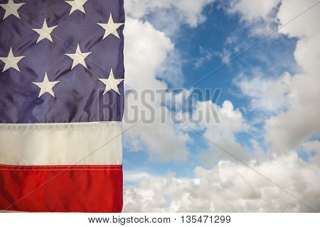 Creased US flag against blue sky with white clouds