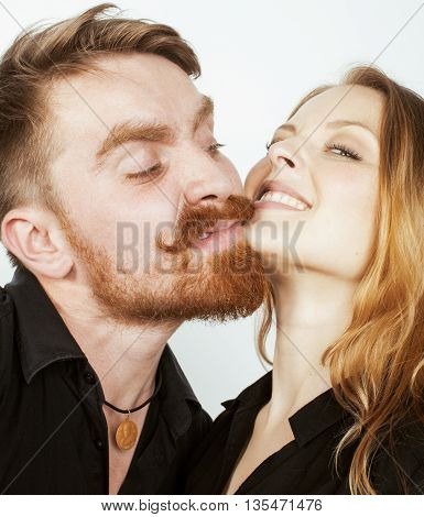 young tender hipster real couple, man and woman in love isolated on white close up kissing smiling fooling around