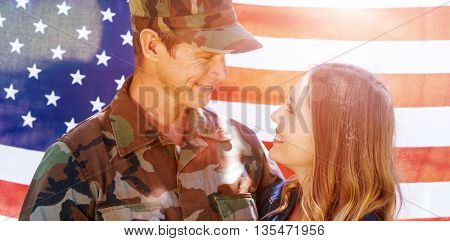 Happy american soldier reunited with his partner in front of american flag