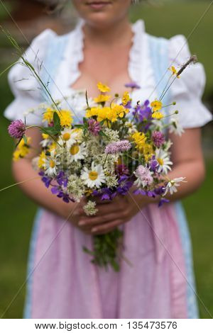 Swiss girl in traditional dirndl with fresh meadow bouquet.