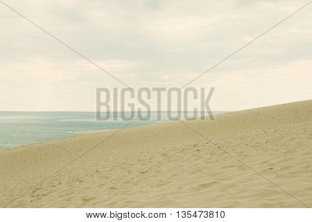Sand sea and sky. Retro styled image.
