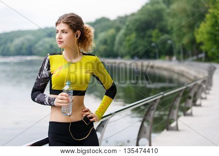 Sporty caucasian girl resting in the Park after Jogging with a plastic bottle of water