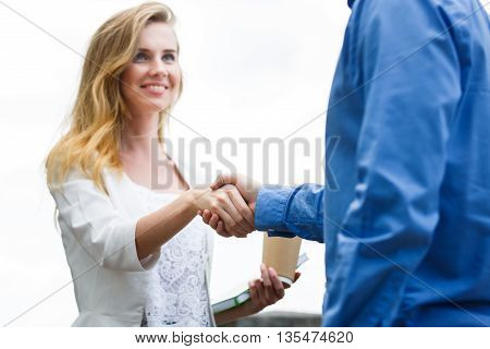 Two people, man and woman give handshake after agreement. Focused on handshake