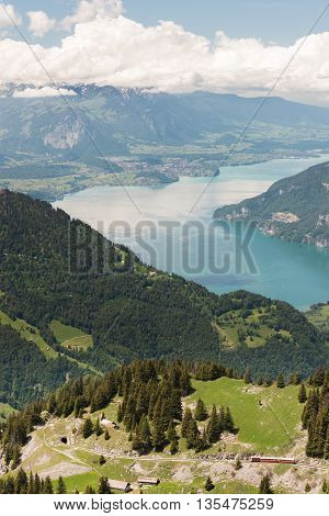 Switzerland Cog Railway trains goes from Schynige Platte to Interlaken through the tunnel with Thunersee lake on background.