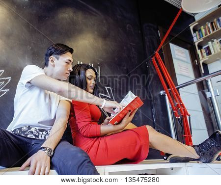 couple students in univercity library, looking book, preparing to exam, having fun, making selfie, lifestyle people