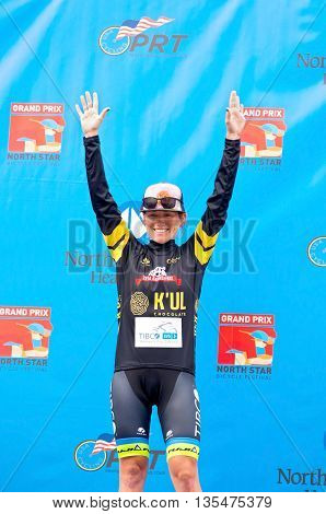 ST. PAUL, MINNESOTA - JUNE 15, 2016: Pro cyclist Lauren Stephens atop winner's podium at North Star Grand Prix time trial in St. Paul on June 15 as she accepts the black jersey for Best Sprinter.