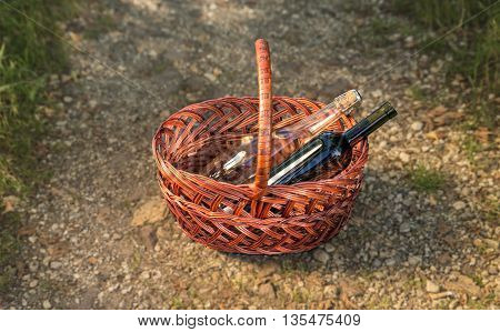 wicker basket with wine, stands on a forest path