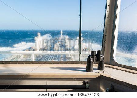 Binocular on the windowsill of navigation bridge against blurred background.