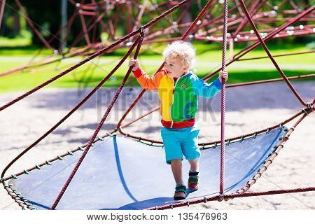 Active little child playing on climbing net and jumping on trampoline at school yard playground. Kids play and climb outdoors on sunny summer day. Cute boy on nest swing at preschool sport center.