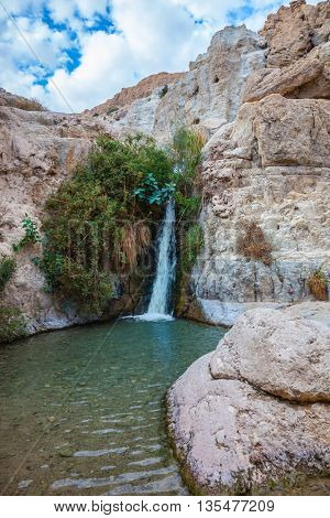 The journey through the national park and reserves Ein Gedi. Adorable waterfall among rocks parched desert