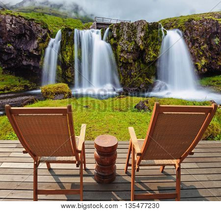 Deck chairs on wooden platform waiting for tourists.  Threaded full-flowing waterfall Kirkyufell Foss on the grassy mountains