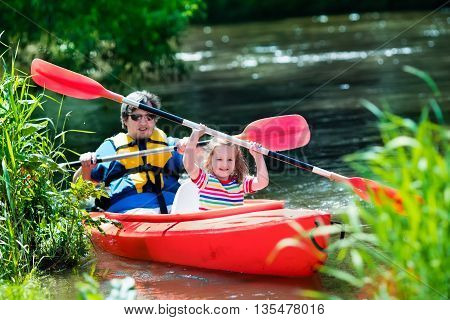 Family on kayaks and canoe tour. Father and child paddling in kayak in a river on a sunny day. Children in summer sport camp. Active preschooler kayaking in a lake. Water fun during school vacation.
