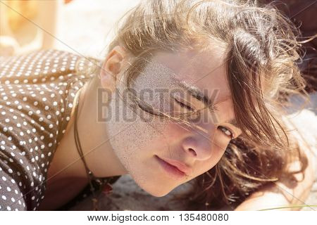woman laying on the beach with sand in her face