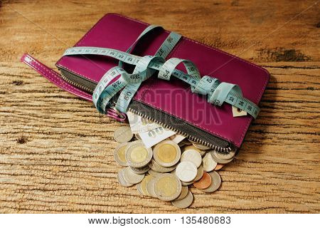 money save concept money in woman bag with measuring tape on woodenwoman bag unlock zipper to half