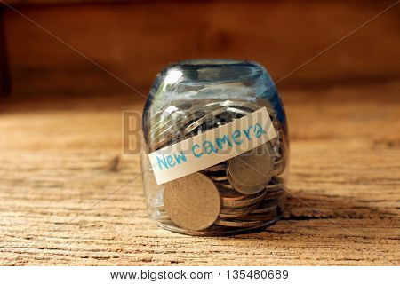 coins in glass with text for new carmera money save concept