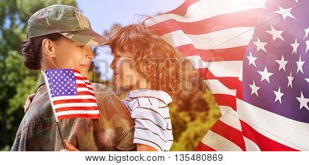 Army woman carrying son against focus on usa flag
