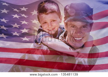Digitally generated american flag rippling against happy soldier giving piggyback to his son