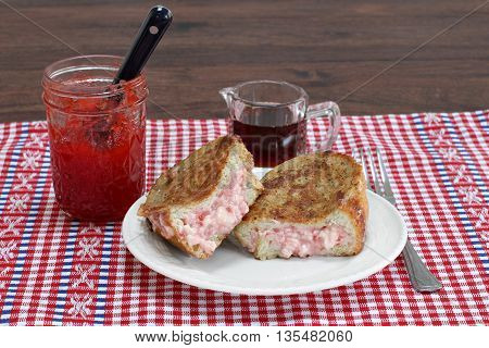 Homemade stuffed french toast with strawberry jam and cream cheese.