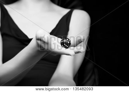 Blurred woman silhouette holding round dice in her hand. Gambling fortune or randomize concept black and white photo