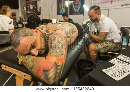 KRAKOW, POLAND - JUNE 11, 2016: Unidentified festival participant make a tattoos at the 11-th International Tattoo Convention in the Congress-EXPO Center of Krakow.