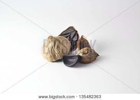 Black garlic whole and cloves grouped on white background
