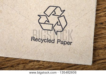 A close-up of a symbol indicating that the item is made from recycled paper.