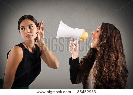 Woman with megaphone shouting to another woman listening