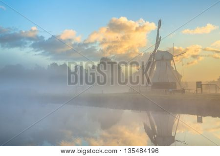 White Wooden Windmill In Morning Fog