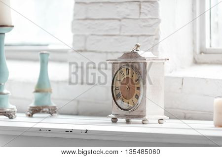light shabby chic  interior fragment with clock and candlesticks on white brick wall background