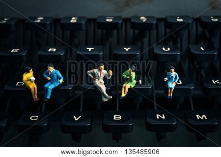 Miniature business people sitting on the typewriter