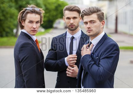 Three young men in elegant business suits, close up portrait, summer street outdoors