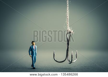 Miniature businessman is staring at fishing needle
