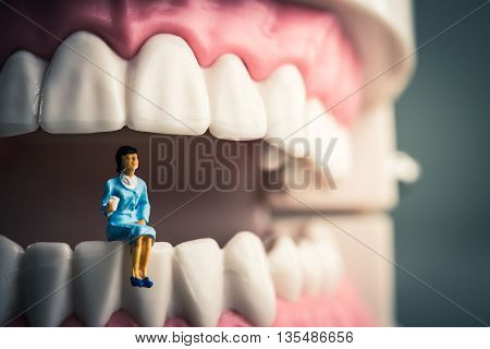 Miniature women sitting on the model of teeth